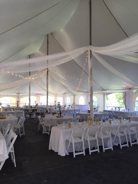 Un grand mariage champêtre sous un beau chapiteau blanc muni de voilages blancs et de petites lumières faisant une ambiance chaleureuse!